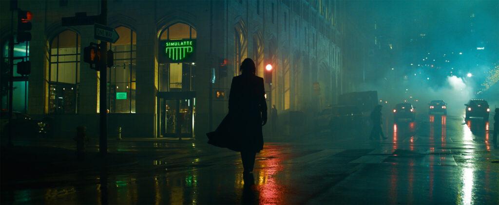 The-Matrix-4-Ressurections-fotograma-Keanu-Reeves-es-Neo-andando-por-la-calle-en-una-noche-de-lluvia