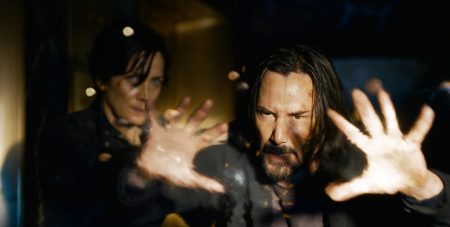 The Matrix 4 Ressurections fotograma Keanu Reeves es Neo Carrie-Anne Moss es Trinity parando balas con las manos abiertas